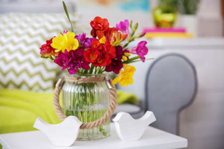 Beautiful freesia flowers on table in room Stock fotó