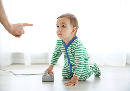 Mother scolding her baby who is playing with plug Stock fotó