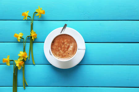Cup of coffee with yellow daffodils on turquoise wooden background Foto de archivo