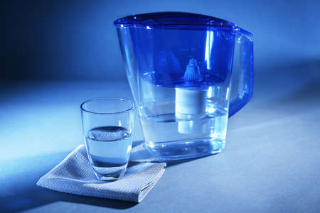 Filter and glass of water on dark blue background Фото со стока