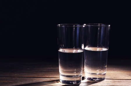 Two glasses of pure water on wooden table