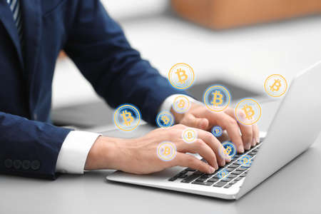 Bitcoin symbols and businessman using laptop at table