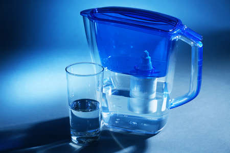 Filter and glass of water on dark blue background Stockfoto