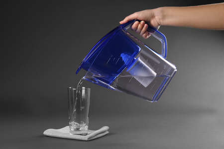 Purified water pouring into glass on grey background Stock Photo