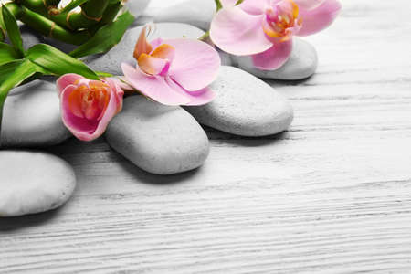 Spa stones, bamboo stack and orchid flowers on wooden background Stockfoto