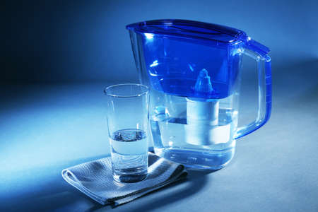 Filter and glass of water on dark blue background Stock Photo