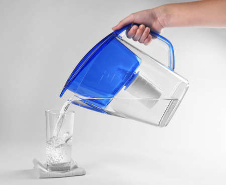 Purified water pouring into glass on white background Stock Photo