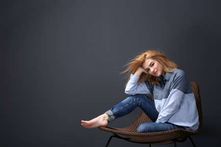 Beautiful young woman in shirt and jeans sitting on chair on dark wall background Standard-Bild