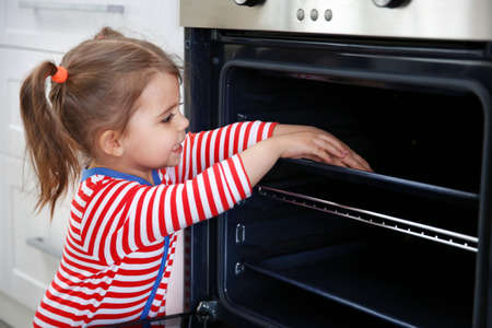 Little girl playing with oven in the kitchen