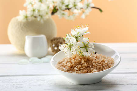 Spa treatment with blooming branch on white wooden table