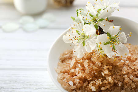 Brown sea salt with blooming flowers on wooden table Stock Photo