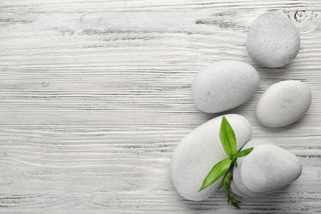 Heap of spa hot stones on white wooden background