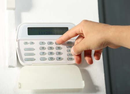 Male hand pressing the code on a house alarm