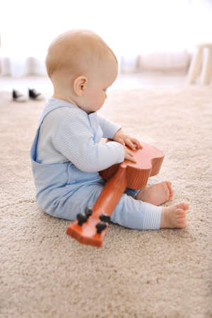 Baby boy playing with toy guitar