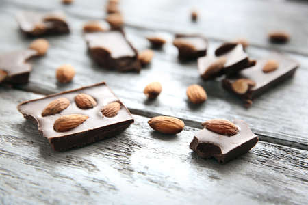 Chocolate pieces with nuts on wooden background Reklamní fotografie