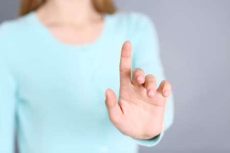 Kobieta ręką dotykając wirtualnego ekranu na szarym tle Zdjęcie Seryjne