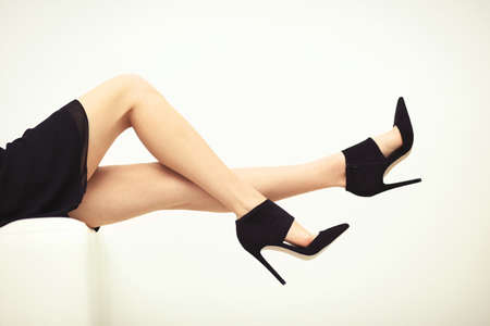 Woman legs in stylish black shoes on white background Stock Photo