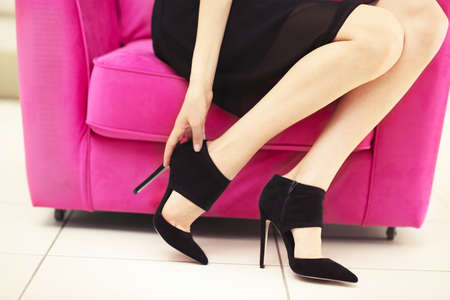 Woman in stylish shoes on pink armchair Stock Photo