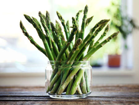 Asparagus in glass jar on wooden table 版權商用圖片 - 95880382