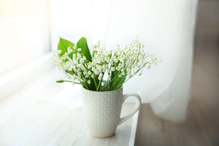 Bouquet of lilies of the valley on windowsill