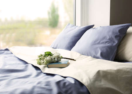 Made-up bed with blue bed linens and book Imagens - 95898618