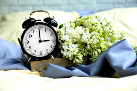 Alarm clock and flower bouquet on  the bed Stock Photo