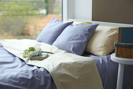 Made-up bed with blue bed linens and book