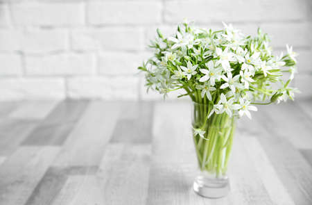 Bouquet of little white flowers on brick wall background