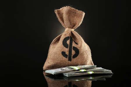 Money bag with dollars on black background Foto de archivo