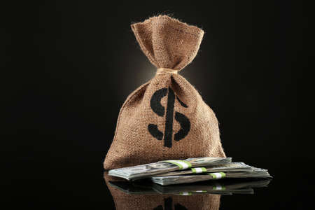 Money bag with dollars on black background Stock Photo