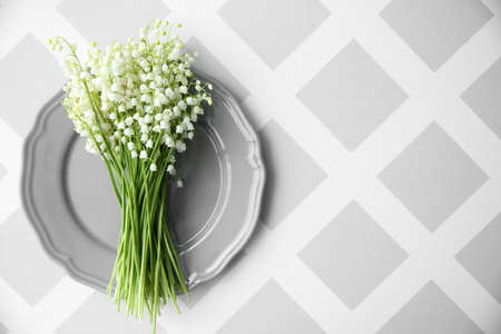 Bouquet of lilies of the valley on gray plate