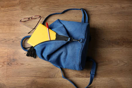 Backpack with accessories on wooden floor Stockfoto