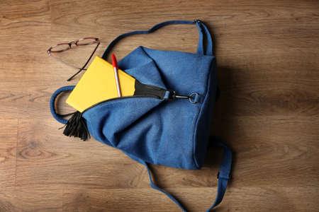 Backpack with accessories on wooden floor Banco de Imagens