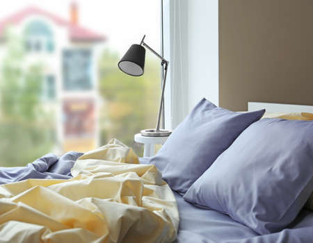 Unmade bed with crumpled blue bed linens Stockfoto