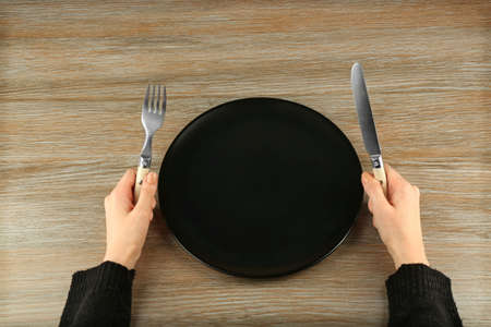 Woman holding fork and knife near empty plate, top view Stock Photo