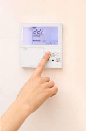 Woman hand on air conditioner remote control