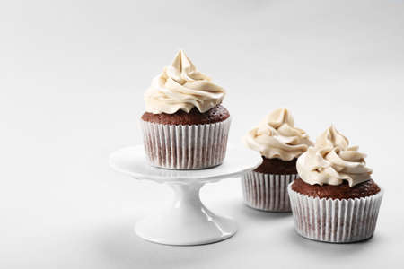 Tasty cupcakes on light background