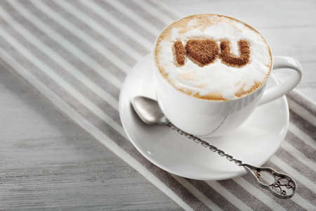 Cup of coffee with creative pattern on wooden table