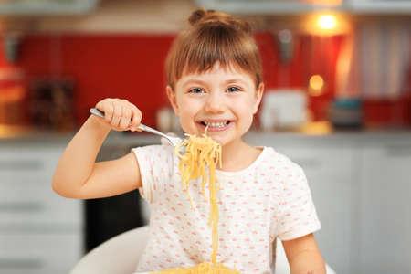 Adorable little girl eating spaghetti in kitchen Stok Fotoğraf
