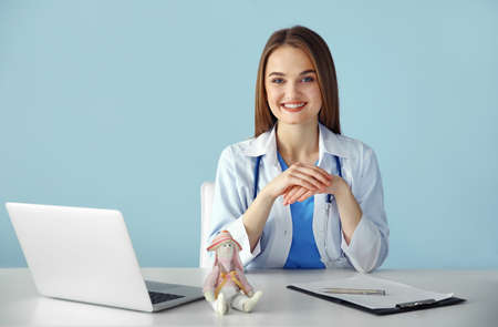 Young beautiful female doctor at the table on wall background Stock Photo