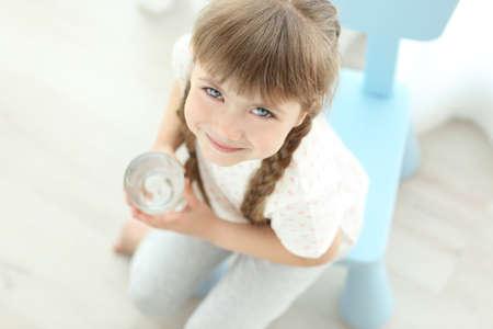 Nettes kleines Mädchen , das Glas Wasser auf hellem Hintergrund hält Standard-Bild - 96095809