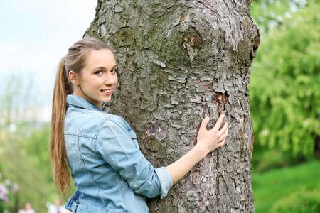 Young beautiful woman hugging tree trunk Stock Photo