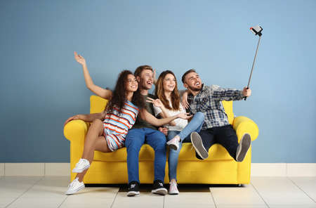 Young cheerful friends taking selfie on yellow sofa in the room Stok Fotoğraf