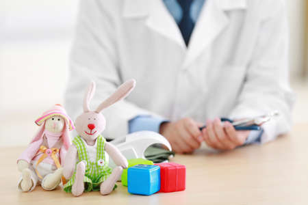 Pediatrician doctor with handmade toys in office