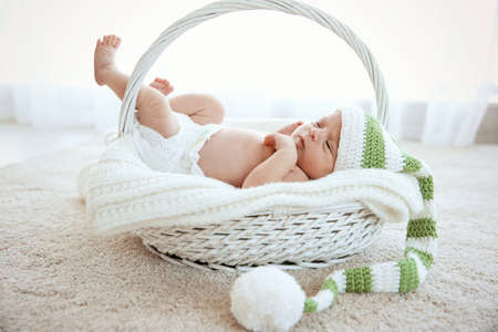 Newborn baby girl, 7 days old, lying on soft blanket in a basket