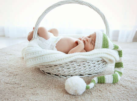 Newborn baby girl, 7 days old, sleeping on soft blanket in a basket