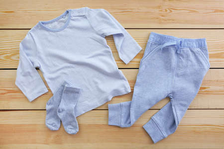 New baby clothes on wooden background