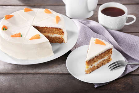 Delicious carrot cake with tea on wooden table