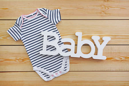 Word baby with clothes on wooden background Reklamní fotografie