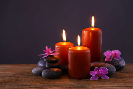 Spa stones with burning candles and flowers on grey background Imagens
